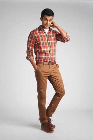 Trend da uomo: Per creare un adatto a un pranzo con gli amici nel weekend indossa una camicia a maniche lunghe scozzese rossa con chino marroni. Ispirati all'eleganza di Luca Argentero e completa il tuo look con un paio di scarpe da barca in pelle marroni.