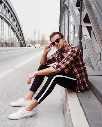 Come indossare e abbinare: camicia a maniche lunghe scozzese rossa e nera, t-shirt girocollo nera, jeans aderenti neri e bianchi, sneakers basse in pelle bianche