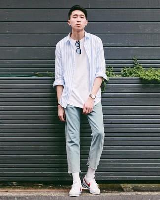 Trend da uomo 2020: Indossa una camicia a maniche lunghe a righe verticali azzurra con jeans azzurri per affrontare con facilità la tua giornata. Questo outfit si abbina perfettamente a un paio di sneakers basse di tela bianche e rosse.
