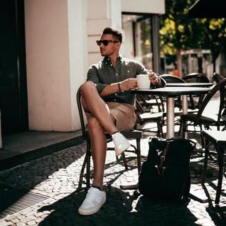 Come indossare e abbinare: camicia a maniche lunghe di lino verde oliva, pantaloncini marrone chiaro, sneakers basse in pelle bianche, zaino di tela nero