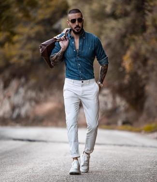 Come indossare e abbinare: camicia di jeans blu, chino bianchi, sneakers basse in pelle bianche, borsone in pelle marrone
