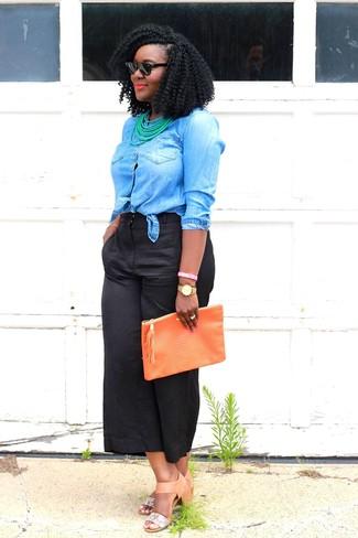 Come indossare: camicia di jeans blu, gonna pantalone nera, sandali con tacco in pelle marrone chiaro, pochette in pelle arancione