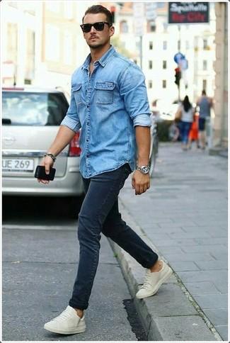 Come indossare e abbinare: camicia di jeans blu, jeans aderenti blu scuro, sneakers basse beige, occhiali da sole neri