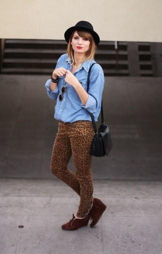 Come indossare: camicia di jeans blu, jeans aderenti leopardati marrone chiaro, stivaletti con zeppa in pelle scamosciata marrone scuro, borsa a tracolla in pelle nera