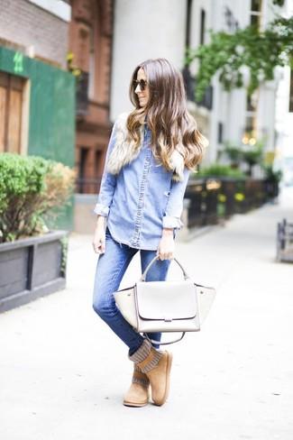 Come indossare: camicia di jeans azzurra, jeans aderenti blu, stivali ugg marrone chiaro, cartella in pelle grigia