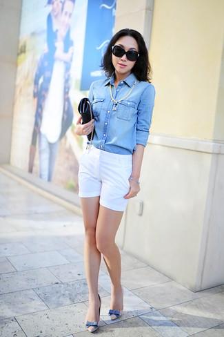 Come indossare e abbinare: camicia di jeans azzurra, pantaloncini bianchi, décolleté in pelle beige, pochette in pelle nera