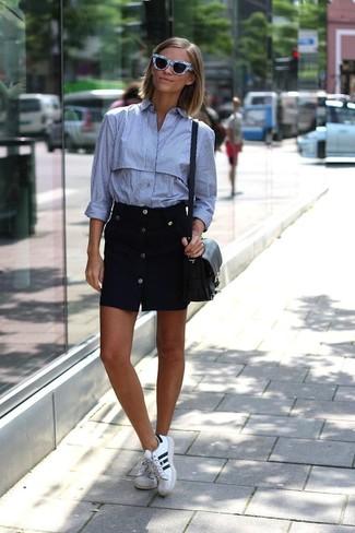Come indossare: camicia elegante a righe verticali azzurra, gonna con bottoni nera, sneakers basse in pelle bianche e nere, borsa a tracolla in pelle nera