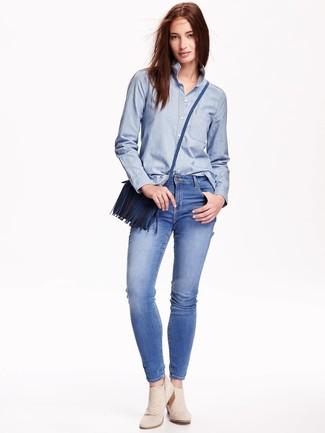 Come indossare: camicia elegante in chambray azzurra, jeans aderenti blu, stivaletti in pelle scamosciata beige, borsa a tracolla in pelle blu