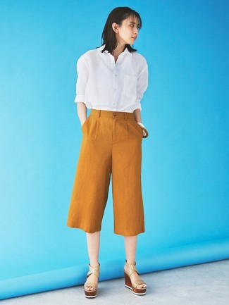 Come indossare: camicia elegante bianca, gonna pantalone terracotta, sandali con zeppa in pelle beige
