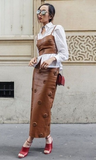 Come indossare e abbinare: camicia elegante bianca, corsetto in pelle marrone, gonna lunga in pelle marrone, sandali con tacco in pelle rossi