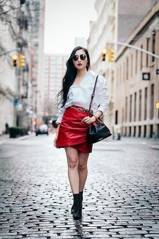Per creare un look adatto a un pranzo con gli amici nel weekend metti una camicia elegante bianca e una minigonna in pelle rossa. Stivaletti in pelle con borchie neri daranno lucentezza a un look discreto.
