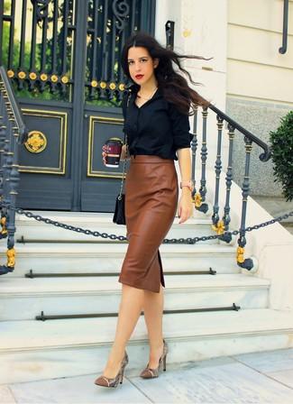 Abbinare una camicia elegante nera con una gonna longuette in pelle marrone è un'ottima opzione per una giornata in ufficio. Un paio di décolleté in pelle con stampa serpente marroni si abbina alla perfezione a una grande varietà di outfit.