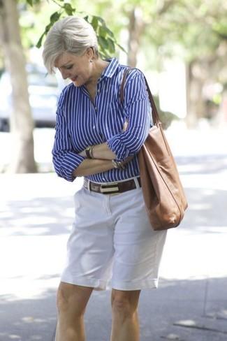 Come indossare e abbinare: camicia elegante a righe verticali blu, pantaloncini bianchi, borsa shopping in pelle marrone, cintura in pelle marrone scuro
