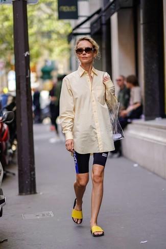 Come indossare: camicia elegante gialla, pantaloncini ciclisti stampati neri, sandali piatti di gomma gialli, borsa shopping di gomma trasparente