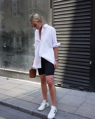 Come indossare: camicia elegante bianca, pantaloncini ciclisti neri, sneakers basse in pelle bianche, borsa a secchiello in pelle marrone