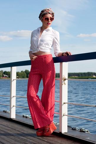 Come indossare: camicia elegante bianca, pantaloni larghi stampati rossi, sandali con zeppa in pelle scamosciata arancioni, sciarpa di seta rossa e bianca