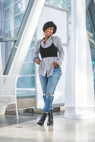 Come indossare: camicia elegante a righe verticali bianca e nera, top corto nero, jeans boyfriend strappati blu, stivaletti in pelle neri
