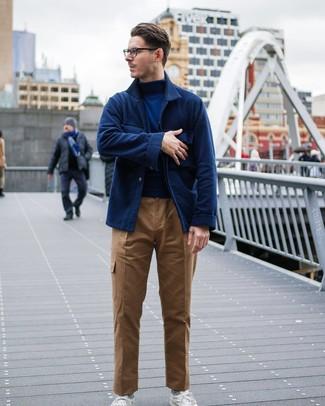 Come indossare e abbinare: camicia giacca di lana blu scuro, dolcevita blu scuro, pantaloni cargo marrone chiaro, sneakers basse bianche