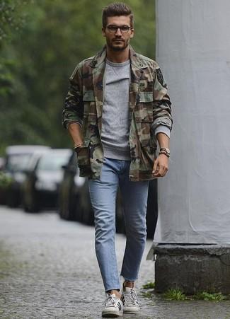 Come indossare e abbinare: camicia giacca mimetica verde oliva, felpa grigia, jeans aderenti azzurri, sneakers basse in pelle bianche