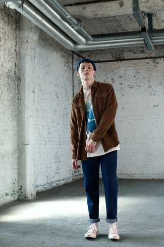Come indossare e abbinare: camicia giacca marrone, t-shirt girocollo stampata bianca e blu, jeans blu, sneakers basse di tela bianche