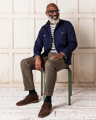 Come indossare: camicia giacca blu scuro, t-shirt manica lunga a righe orizzontali bianca e nera, chino marroni, chukka in pelle scamosciata marrone scuro