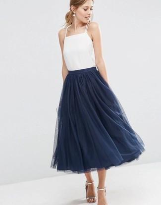 Come indossare: canotta di seta bianca, gonna a ruota in tulle blu scuro, sandali con tacco in pelle argento