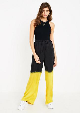 Come indossare: canotta nera, pantaloni larghi effetto tie-dye gialli, scarpe sportive bianche, collana con ciondolo dorata