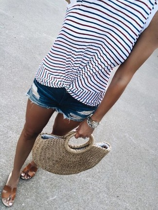 Come indossare e abbinare: canotta a righe orizzontali bianca, pantaloncini di jeans strappati blu, sandali piatti in pelle marroni, borsa shopping di paglia marrone chiaro
