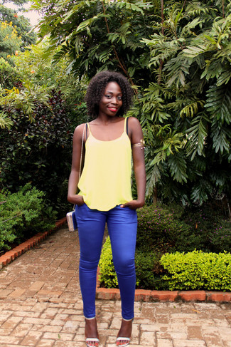 Come indossare: canotta gialla, pantaloni skinny blu, sandali con tacco in pelle argento, borsa a tracolla in pelle blu