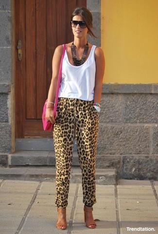 Come indossare e abbinare: canotta bianca, pantaloni stretti in fondo leopardati marrone chiaro, sandali con tacco in pelle marroni, borsa a tracolla in pelle fucsia