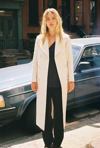 Come indossare: cappotto beige, maglione con scollo a v grigio scuro, pantaloni larghi neri, sandali con tacco in pelle neri