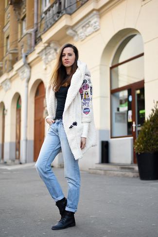Come indossare: cappotto di pile bianco, camicetta manica lunga nera, jeans boyfriend azzurri, stivali piatti stringati in pelle neri