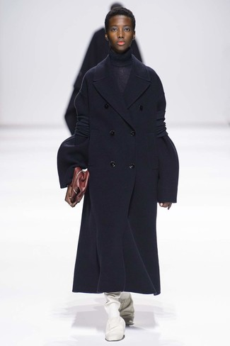 Come indossare: cappotto blu scuro, dolcevita lavorato a maglia blu scuro, stivali al ginocchio in pelle bianchi, pochette in pelle bordeaux
