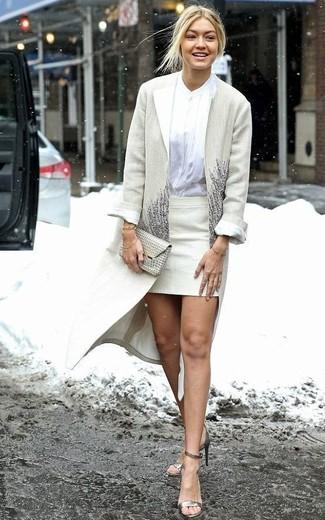 Come indossare: cappotto beige, blusa abbottonata bianca, minigonna beige, sandali con tacco in pelle dorati