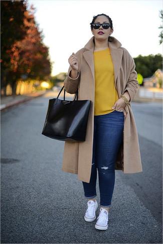Come indossare e abbinare: cappotto marrone chiaro, camicetta manica corta gialla, jeans aderenti strappati blu scuro, sneakers basse di tela bianche