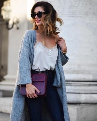 Come indossare e abbinare: cappotto lavorato a maglia grigio, canotta di seta grigia, jeans aderenti blu scuro, cartella in pelle melanzana scuro