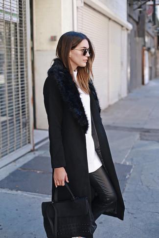 Come indossare e abbinare: cappotto con collo di pelliccia nero, maglione girocollo bianco, pantaloni skinny in pelle neri, cartella in pelle nera