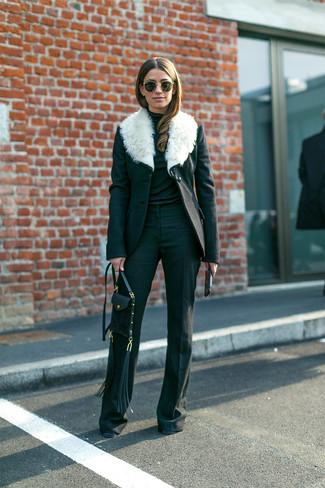 Come indossare e abbinare: cappotto con collo di pelliccia nero e bianco, dolcevita nero, pantaloni a campana neri, borsa a tracolla in pelle nera