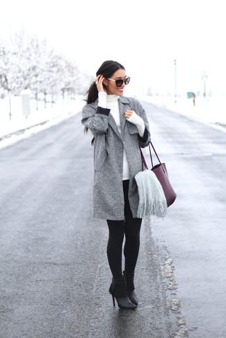 Come indossare: cappotto grigio, dolcevita bianco, leggings neri, stivaletti in pelle con frange neri