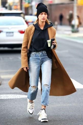 Come indossare: cappotto marrone chiaro, felpa con cappuccio nera, jeans boyfriend strappati azzurri, scarpe sportive bianche