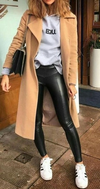Come indossare e abbinare: cappotto marrone chiaro, felpa con cappuccio stampata grigia, leggings in pelle neri, sneakers basse in pelle bianche e nere