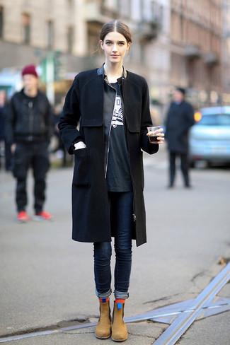 Come indossare e abbinare: cappotto nero, giacca da moto in pelle nera, t-shirt girocollo stampata nera e bianca, jeans aderenti blu scuro