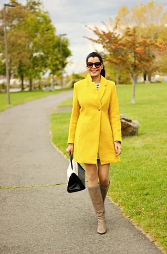 Come indossare e abbinare: cappotto giallo, stivali al ginocchio in pelle marrone chiaro, cartella in pelle bianca e nera