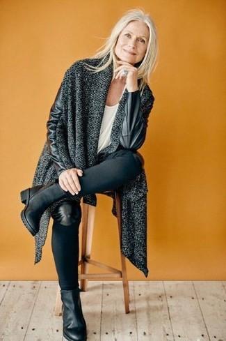 Come indossare e abbinare: cappotto lavorato a maglia grigio scuro, t-shirt girocollo bianca, jeans aderenti neri, stivaletti in pelle neri