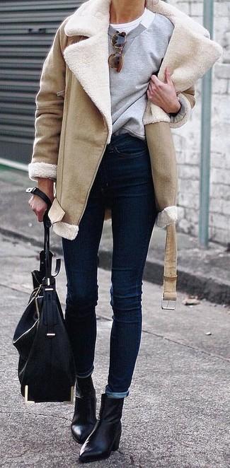 Come indossare e abbinare jeans aderenti blu scuro: Indossa un cappotto in shearling marrone chiaro con jeans aderenti blu scuro per un look raffinato per il tempo libero. Perfeziona questo look con un paio di stivaletti in pelle neri.