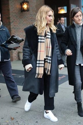 Come indossare: cappotto in shearling nero, maglione oversize lavorato a maglia beige, pantaloni larghi neri, sneakers basse in pelle bianche