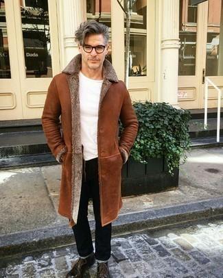 Trend da uomo quando fa gelo: Per un outfit quotidiano pieno di carattere e personalità, vestiti con un cappotto in shearling terracotta e jeans neri. Sfodera il gusto per le calzature di lusso e mettiti un paio di stivali casual in pelle marrone scuro.