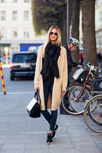 Come indossare: cappotto beige, jeans aderenti blu scuro, scarpe sportive blu scuro, cartella in pelle nera e bianca