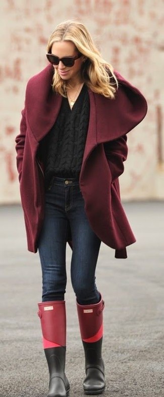 Come indossare: cappotto bordeaux, maglione a trecce nero, jeans aderenti blu scuro, stivali di gomma bordeaux