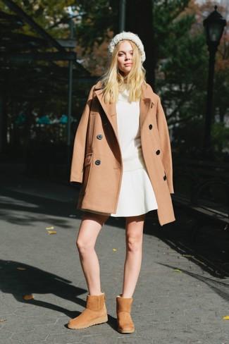 Come indossare: cappotto marrone chiaro, maglione con scollo a cappuccio bianco, gonna a pieghe bianca, stivali ugg marrone chiaro